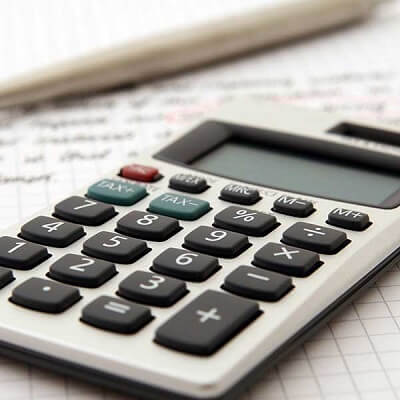 Calculator, pen, and paper, used to calculator home energy efficiency in Frisco, Texas