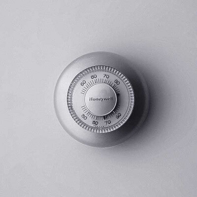 Circular thermostat on blank gray wall